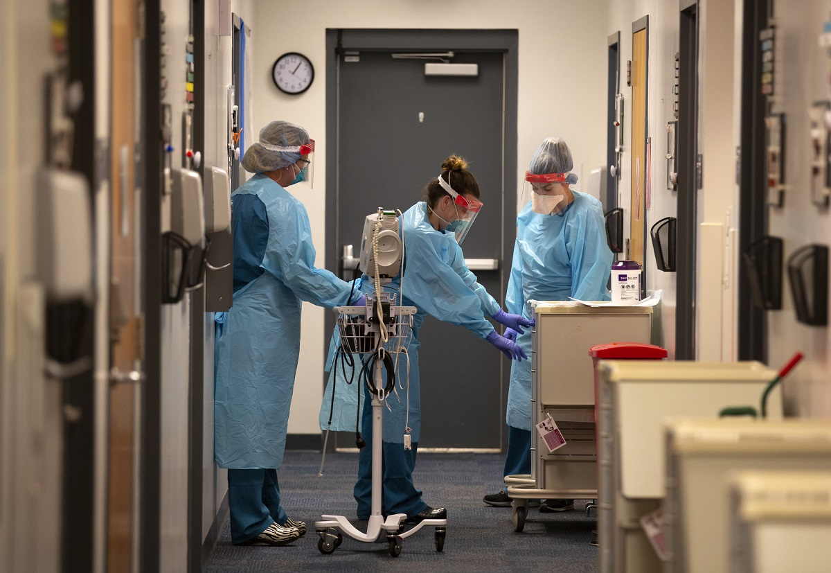 Three nurses in gowns, gloves and face masks stand outside a patient room. The nurse on the left touches a pole with equipment. The nurse in the middle leans over and touches a cabinet, while the nurse on the right watches her.
