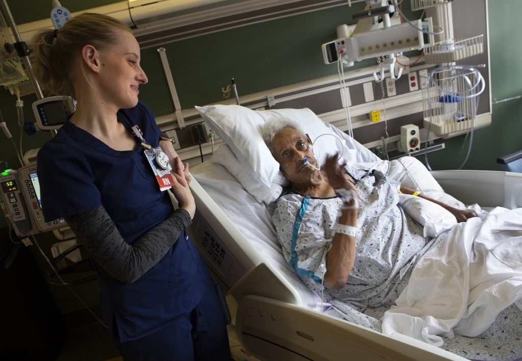 Stroke patient Gracie Banks waves from her hospital bed toward a monitor on the wall. She wears a hospital gown and is connected to tubing and equipment by her bed. Registered nurse Sara Myers, wearing scrubs and her hair in a ponytail, smiles and leans on the hospital bed.