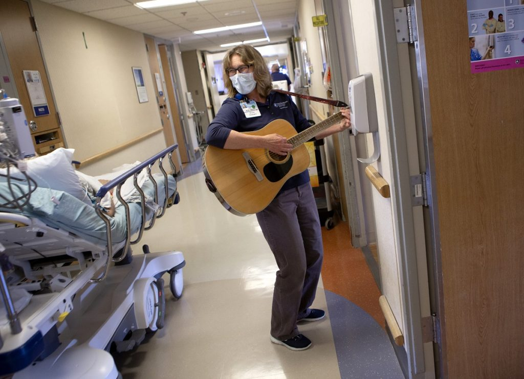 Jan Stouffer, wearing a face mask, strums a guitar and looks toward a patient on a rolling bed in the hallway of a hospital floor. She has glasses and shoulder-length wavy hair.