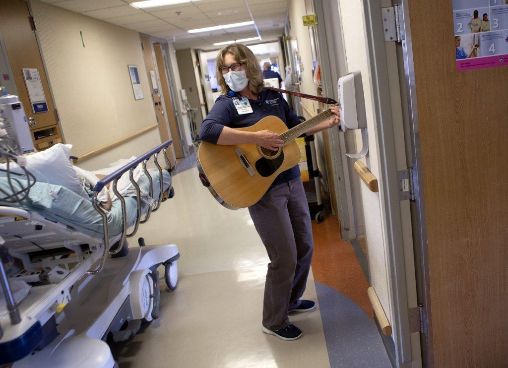 Jan Stouffer, con una máscara facial, toca la guitarra y mira a un paciente en una cama rodante en el pasillo del piso de un hospital. Ella tiene gafas y cabello ondulado hasta los hombros.