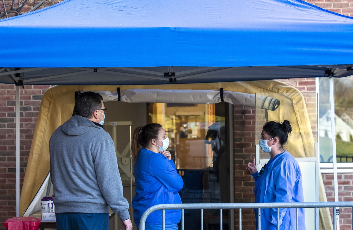 One man and two women radiologic technologists stand under a tent outside the Radiology Annex. The man is wearing a sweatshirt, and the women are wearing scrubs. All three are wearing face masks. The tent is open on all four sides, and a brick building is behind it.