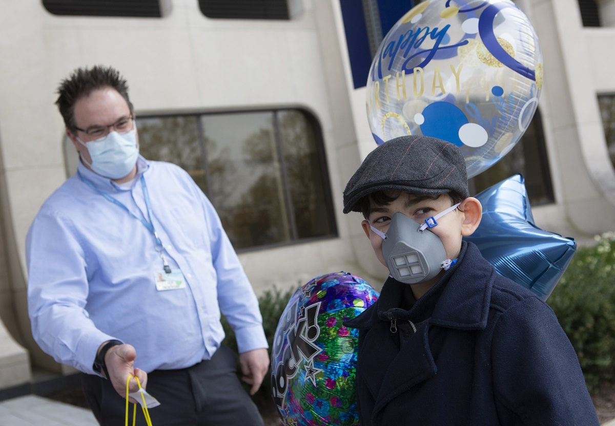 A boy wearing an N95 mask, a cap and coat smiles. Behind him are balloons and a man wearing a mask.