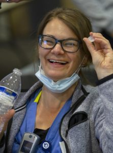 A woman smiles as she holds a water bottle and cap. She is wearing glasses, a surgical mask pulled below her chin, a jacket and scrubs and has a cell phone hanging from her shirt.