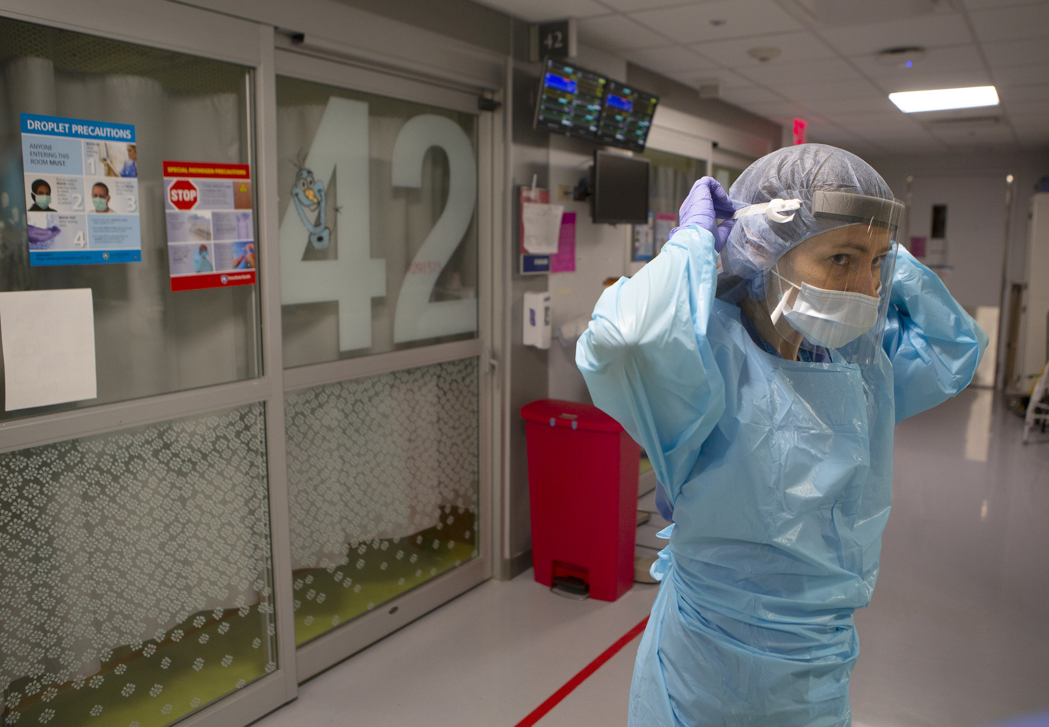 Dr. Jennifer Cooper adjusts her personal protective equipment outside a hospital room.