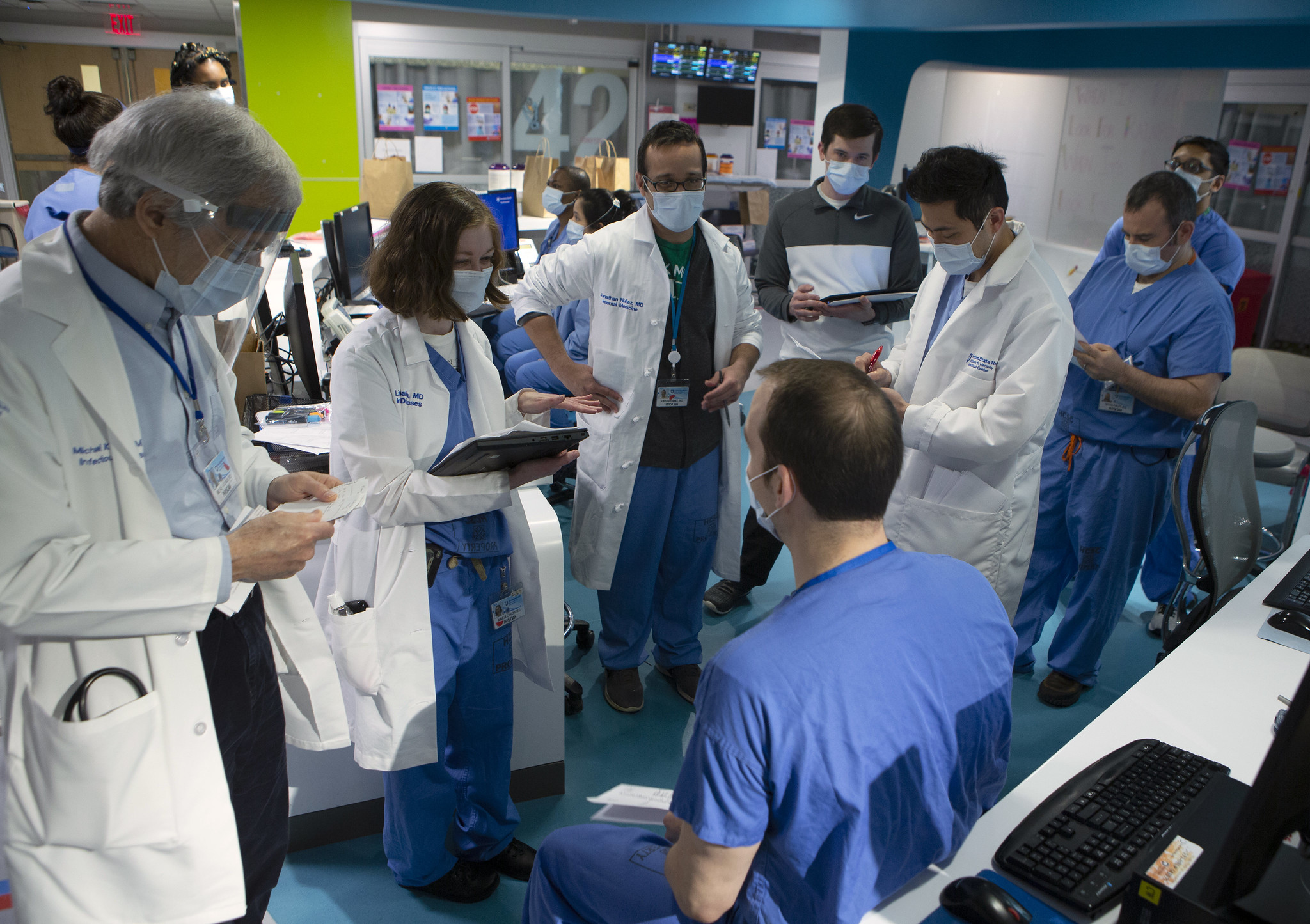 Men and women in scrubs stand in a circle in a hospital common area and look at documents.