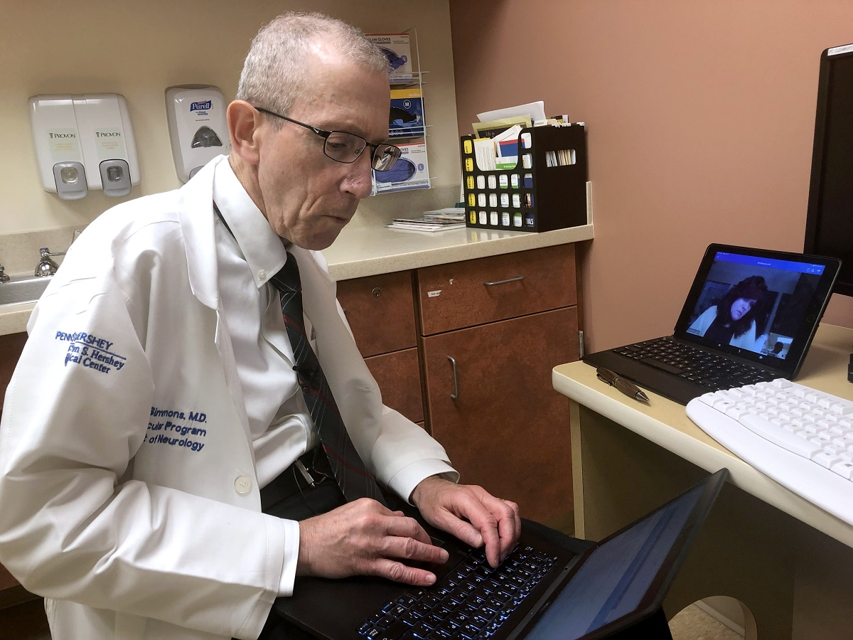 Dr. Zachary Simmons, director of the Penn State ALS Clinic, sits and types on a laptop. He is wearing a white lab coat with the Hershey Medical Center logo on it. A woman is on the screen of another laptop on a counter next to him.