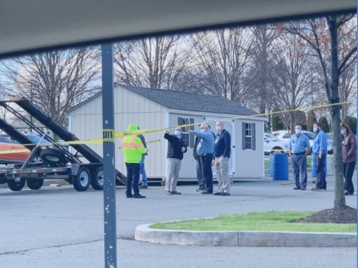 Eight St. Joseph Medical Center employees stand in a parking lot and point to the left. Behind them is a shed. Yellow hazard tape is in the foreground.