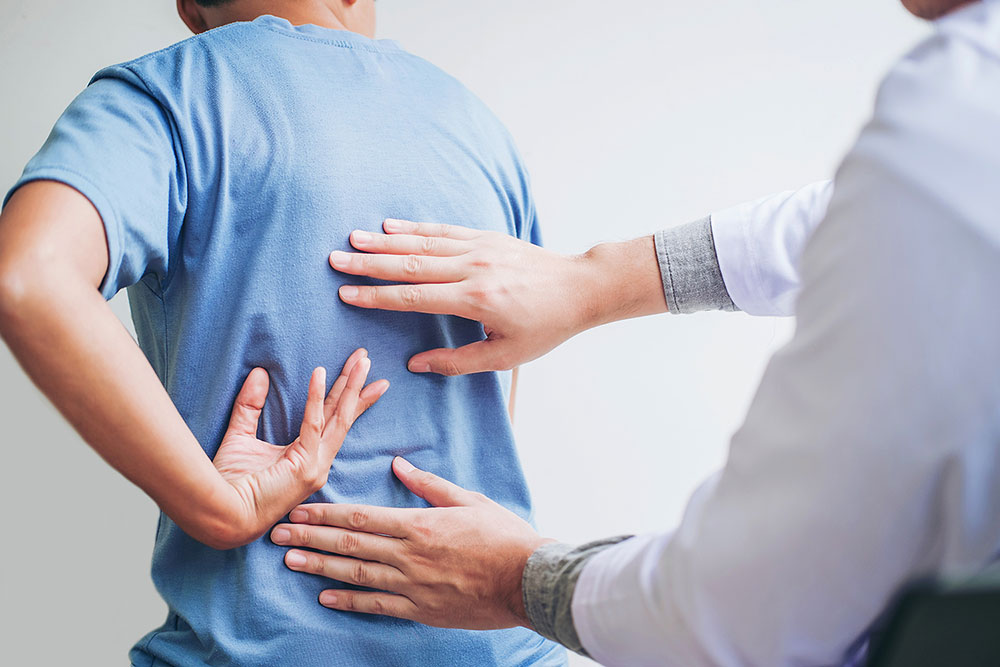 A patient places hand on his back as doctor touches two other spots on the man's back in this stock image.