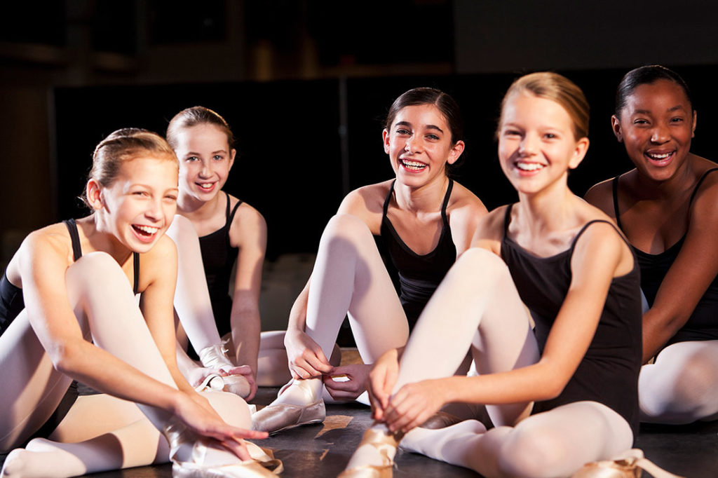 Five young ballet dancers sit on the floor to adjust their dance shoes in this stock image.