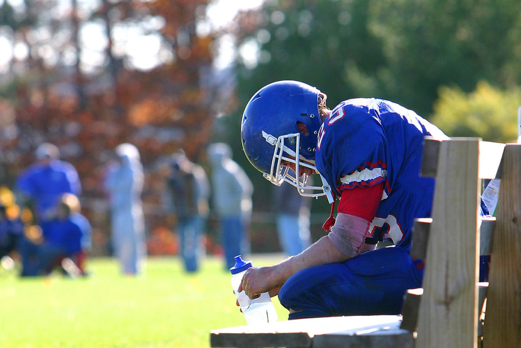 A high school football player sits on bench during game looking down at his water bottle in this stock image.