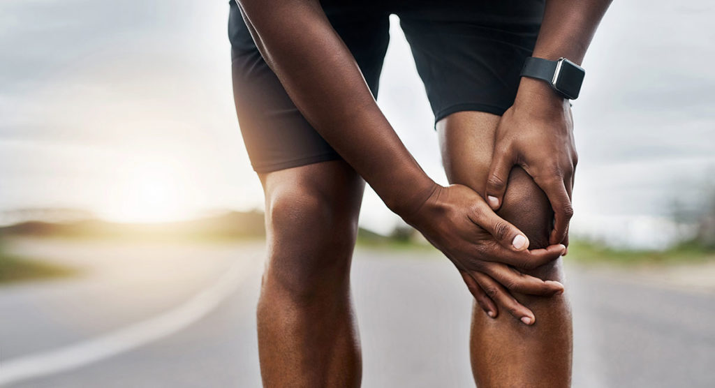 A runner braces his left knee with his hands while stopped on the road in this stock image.