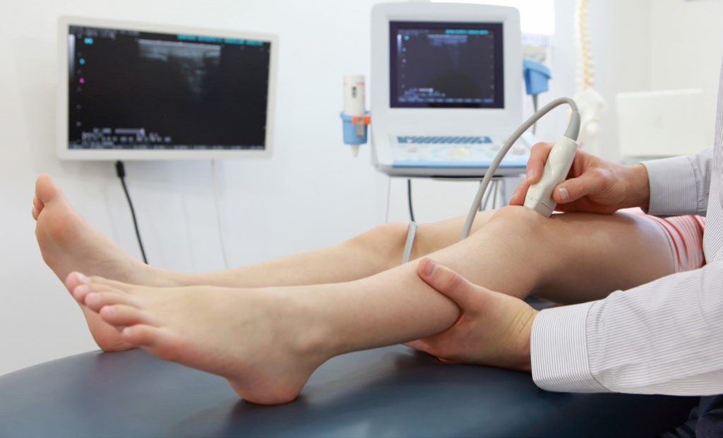 A knee ultrasound is being performed in this stock image.