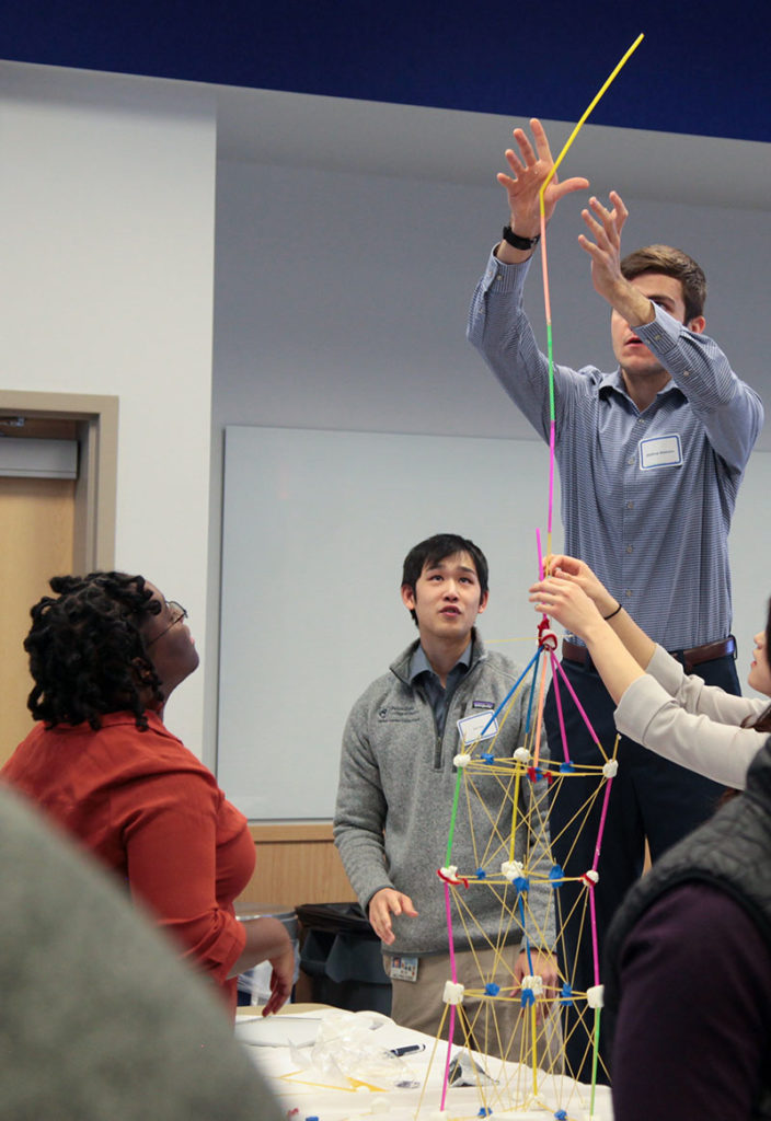A male student is seen balancing straws atop each other with sticky material connecting them to form the framework of a tower. Other students are looking up at him as he reaches for the top of the tower.