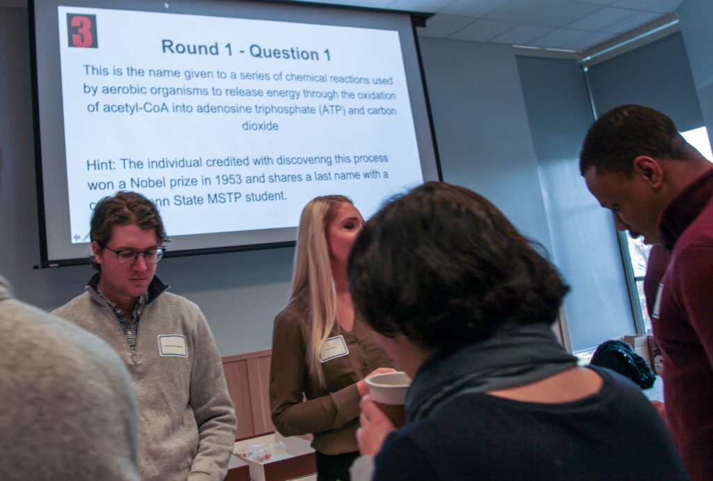 Two students face away from a presentation screen with a science trivia question on it. Other students face the screen.