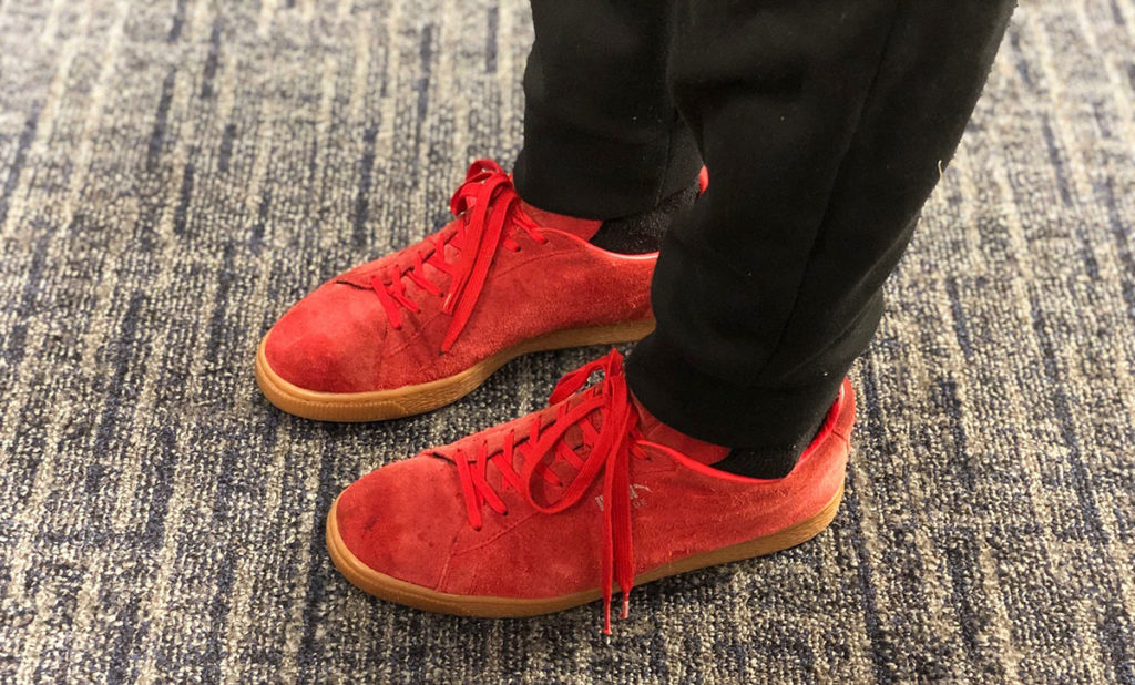 A closeup photo shows a pair of red sneakers on someone's feet.