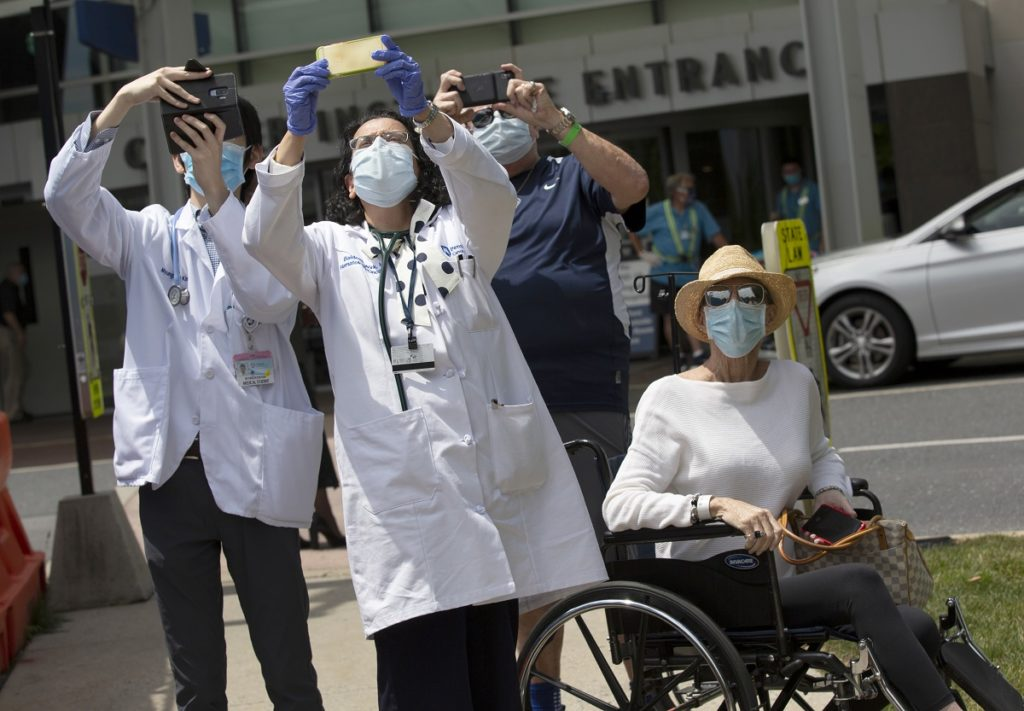 Medical personnel in white coats and Don Donagher hold up cameras toward the sky outside Hershey Medical Center. Lynda Donagher sits in a wheelchair next to them.