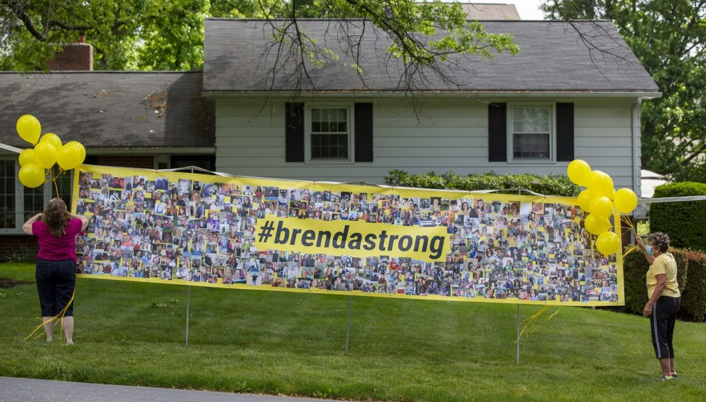 "Two women stand at either end of a sign on wooden posts. They attach balloons to the edges of the sign, which sits on a lawn in front of a small house. The sign says ""#brendastrong"" and is awash in photos."