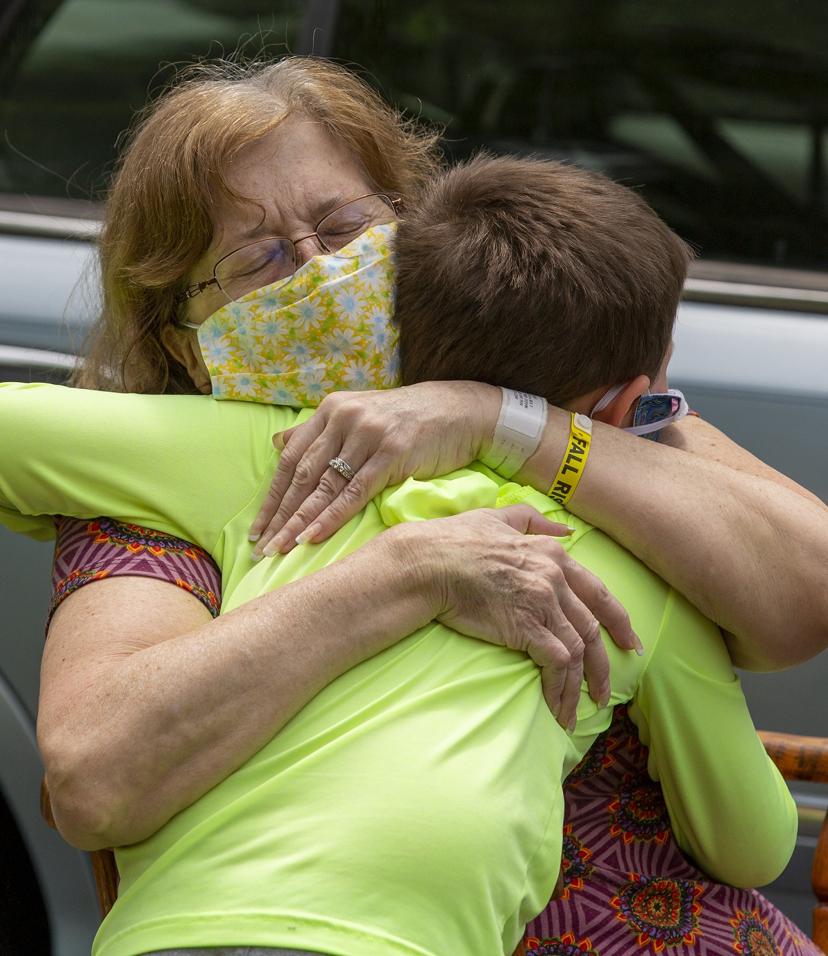 A woman in a surgical mask squeezes her eyes closed as she embraces a young boy.