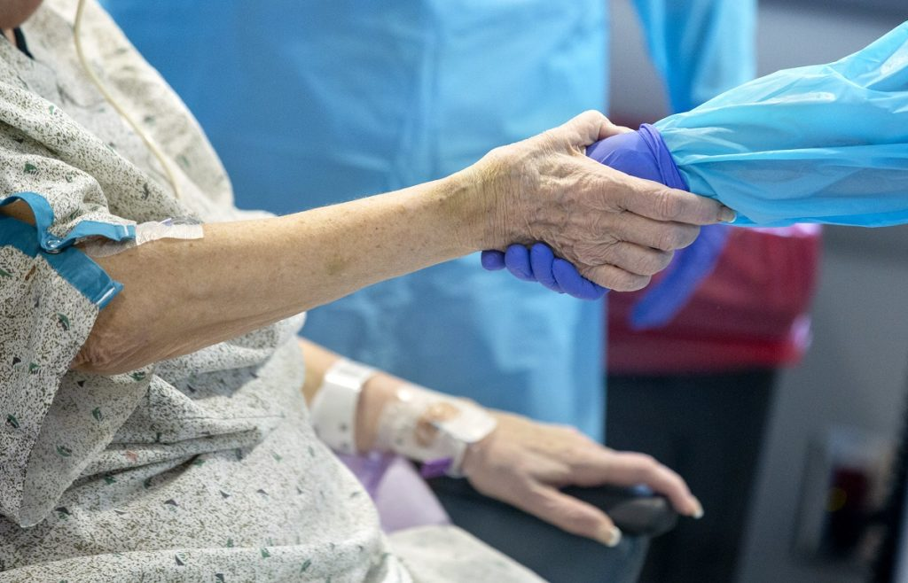 Heather Hahn's gloved hand holds the hand of someone in a hospital gown.