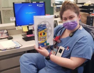 A woman wearing a medical face mask and scrubs sits at a desk, holding a packet with colored pencils and coloring sheets.