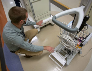 Justin Soulier, nurse manager for the Nursing Vascular Access Team, explains how the hitch on the motorized cart, left, connects to an ultrasound machine for transit.