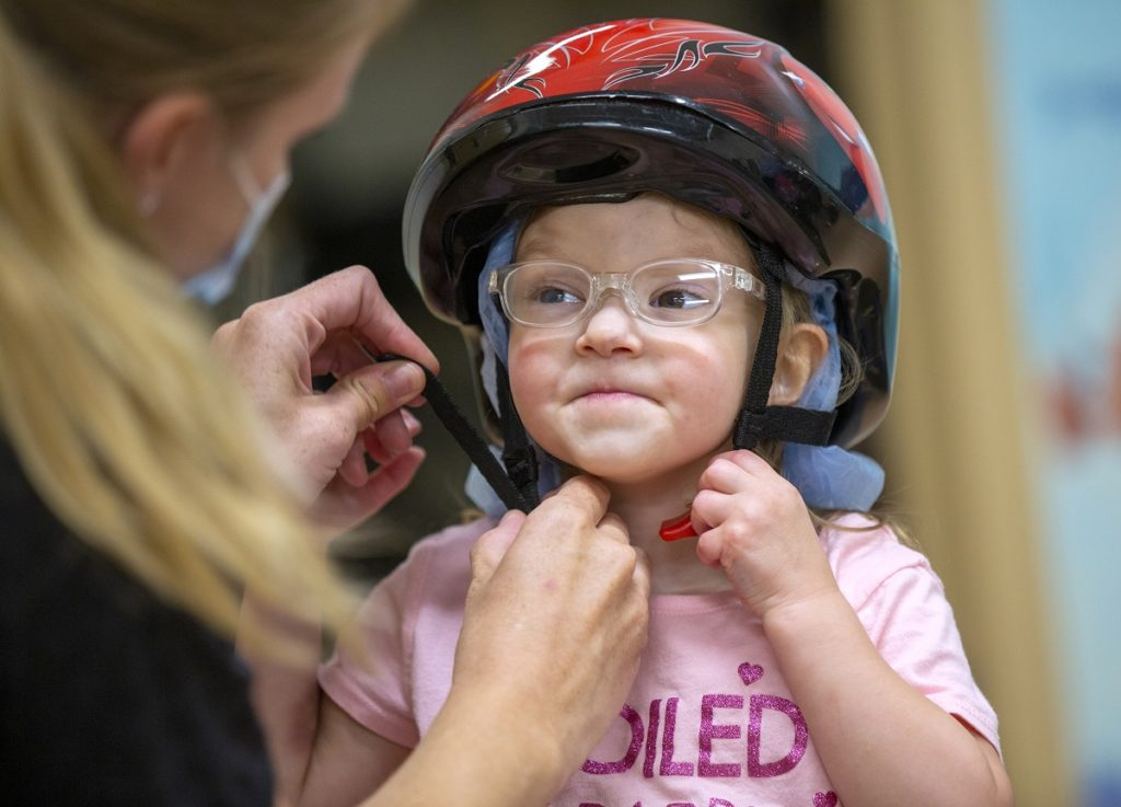 Joella Migliori, who is wearing a bike helmet, purses her lips and holds the buckle of the helmet strap in one hand under her chin. Physical therapist Emily Hoffman, seen from behind, holds the other end of the strap.