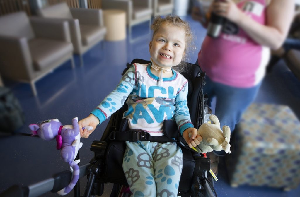 Mya, wearing pajamas with paw prints, gives a tooth grin. She holds stuffed animals in each hand as she sits in a wheelchair.