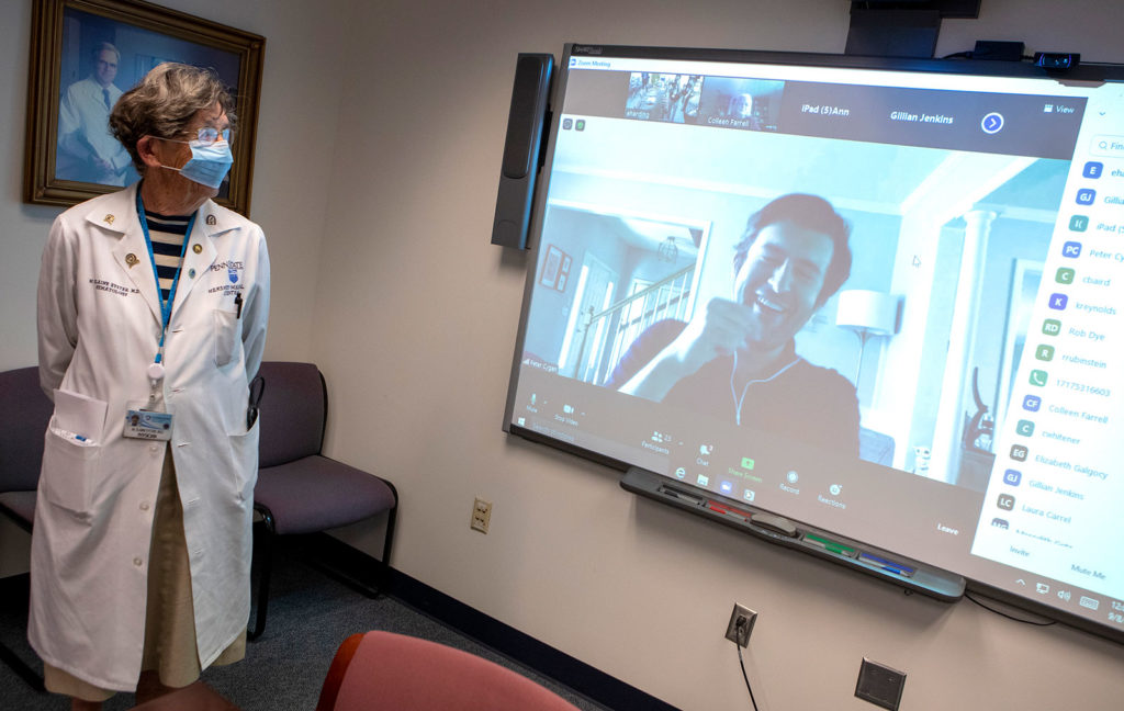 An older woman looks at a large screen in a conference room, where a man's face appears. Both are laughing.