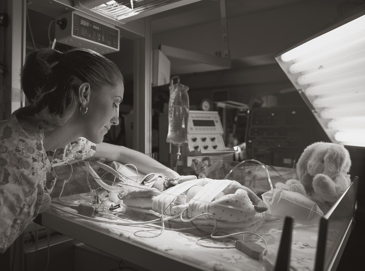 A nurse, wearing scrubs patterned with cartoon pictures of infants, looks over the bassinet of a baby in the Neonatal Intensive Care Unit. Tubing runs from equipment in the background to the baby, who is lying on his back and wears tiny cardboard sunglasses over his face.