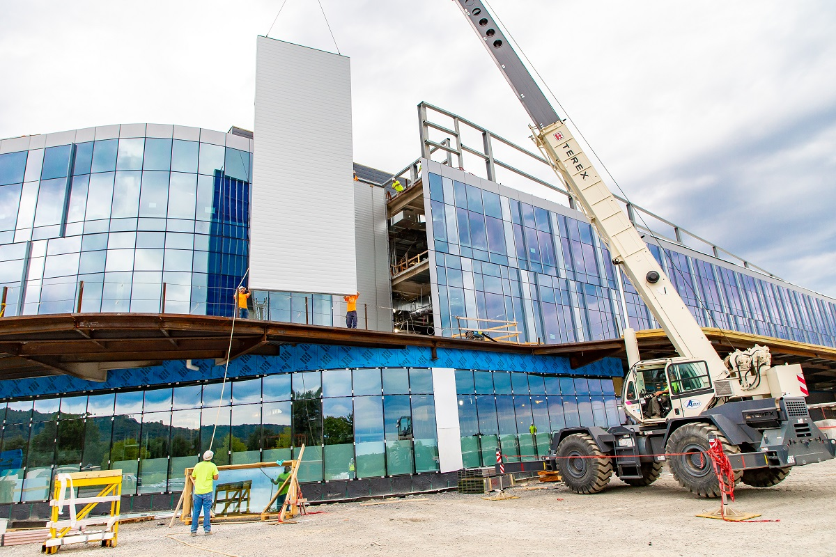 A crane lifts a glass panel into place at the front of the Hampden Medical Center. A worker wearing a hardhat stands on the ground, looking up toward the sky.