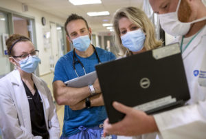 Four clinical staff -- two men and two women -- stand in a hospital hallway, looking at a laptop computer being held by one of them.