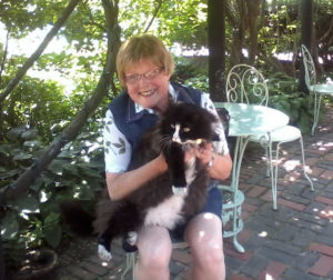 Glenna Brensinger sits on a chair on a brick patio on a sunny day, holding a cat in her lap and smiling. Trees and other vegetation are in the near background.