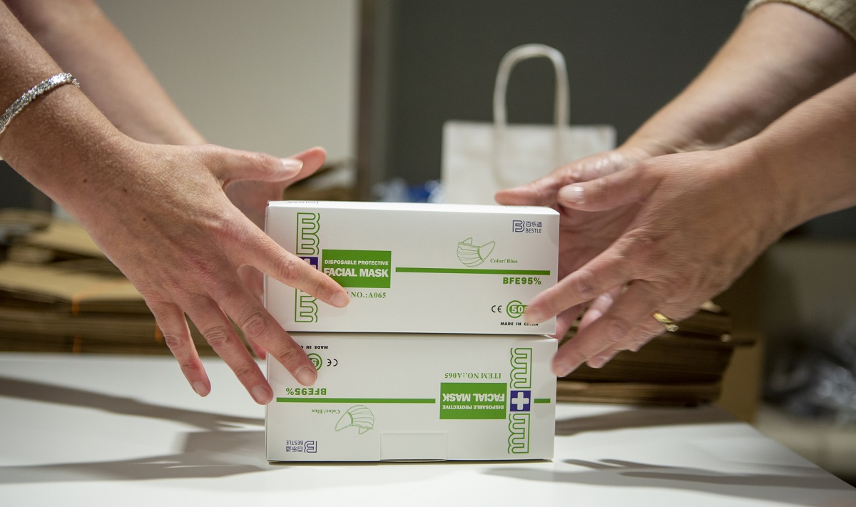 "Hands reach for boxes marked ""Disposable Protective Facial Mask"" positioned in a stack on a table.]"
