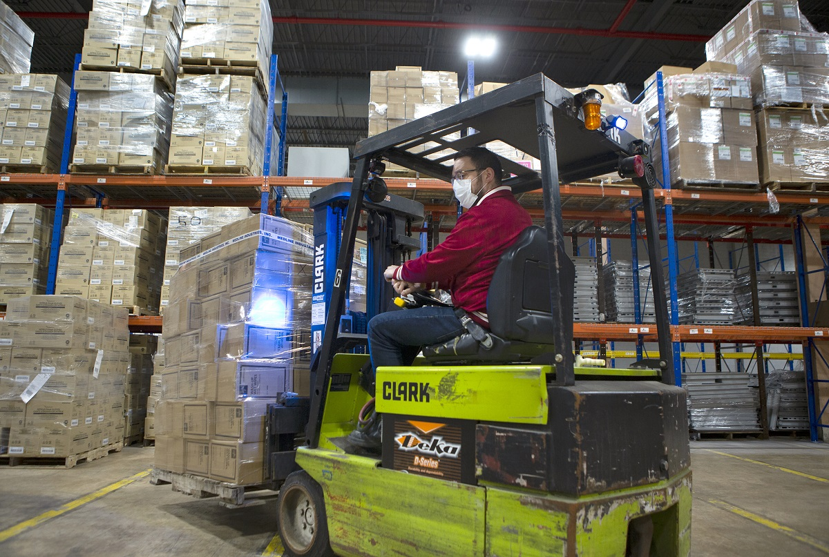 A man driving a forklift wears a surgical mask as the machine moves a pallet loaded with boxes. Shelves loaded with more containers rise above him under a warehouse's fluorescent lights.