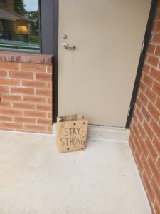 """A paper bag with the words """"Stay Strong"""" written on it sits outside a door of a brick building."""