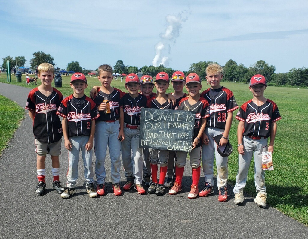 Ten boys dressed in baseball caps and uniforms stand in a line and hold a sign asking for donations to help a teammate's dad who was diagnosed with cancer. A green field is in the background.