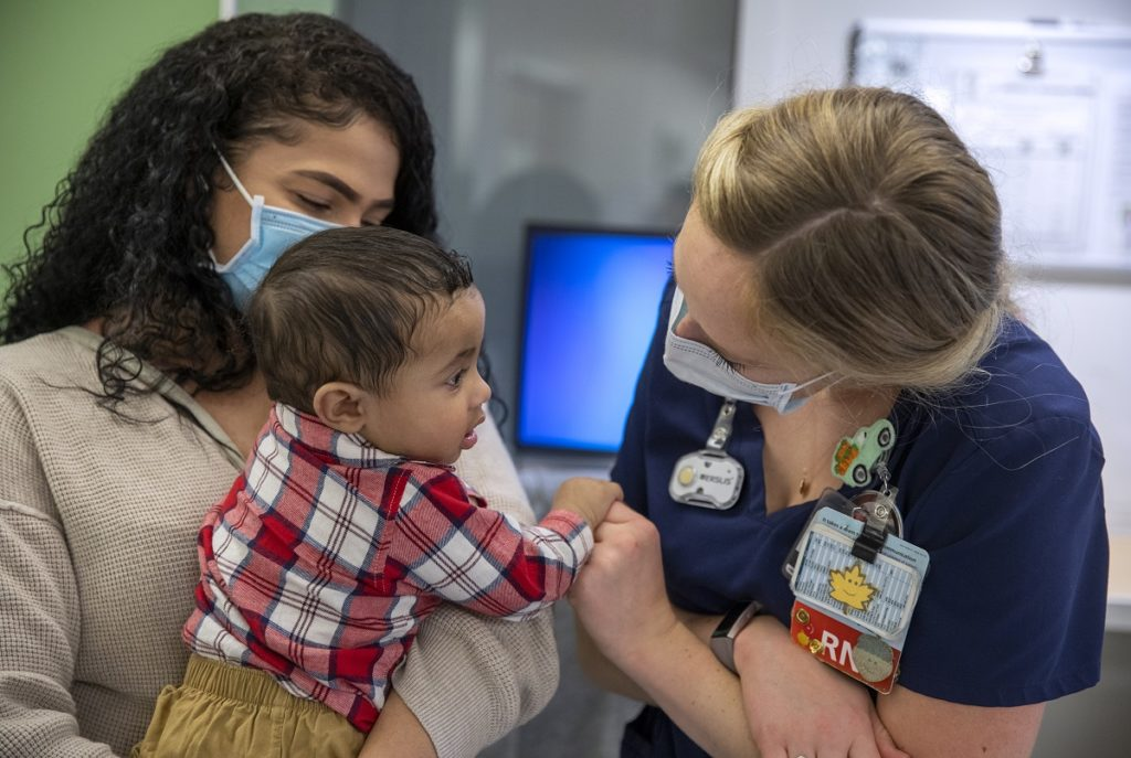 Nurse Jo Rosenberger leans in to hold hands with baby Calvin, being held by his mother, Terianny Vicente. Rosenberger, whose face is not shown, has blonde hair in a ponytail and wears scrubs and a mask.
