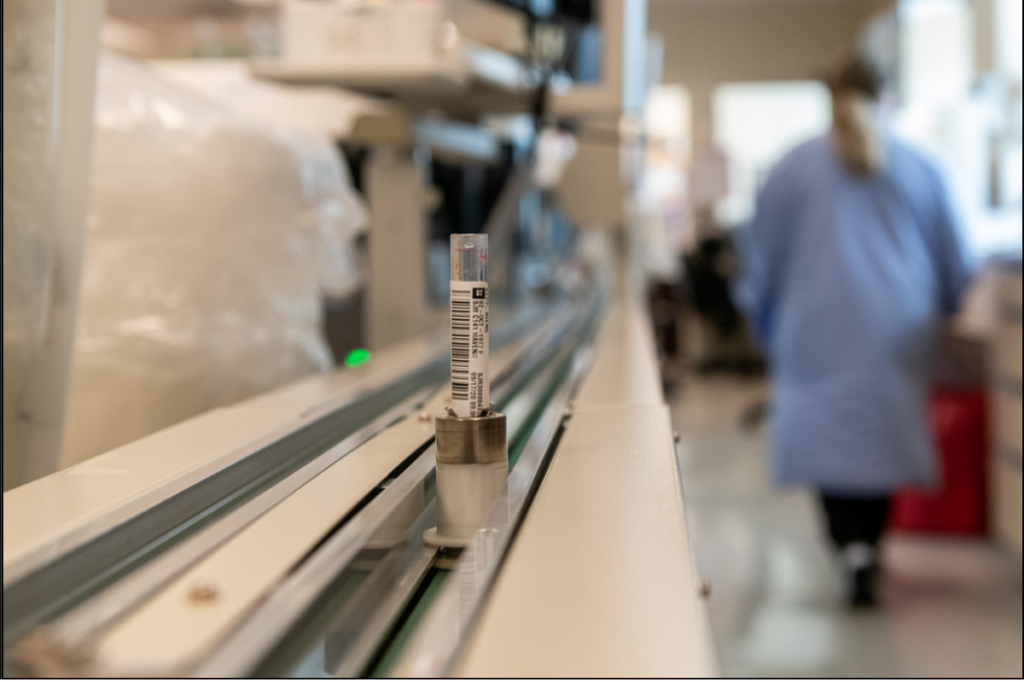 A vial is propped on a conveyor belt. In the background, someone in a lab coat is walking away out of focus.