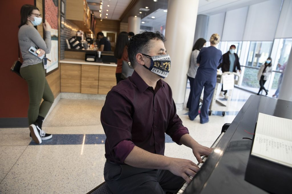 A man in a mask plays a piano while behind him others listen and buy coffee from a counter.