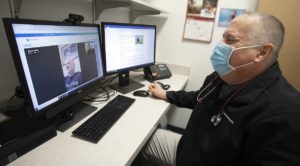 Man seated wearing a black jacket and a facemask with a stethoscope around his neck smiles at his computer screen. Man with blue shirt and grey beard is smiling on screen during a virtual hybrid cardiac rehabilitation appointment.
