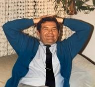 Dr. John Connor, professor emeritus, is seen smiling and leaning back with his hands interlaced behind his head.