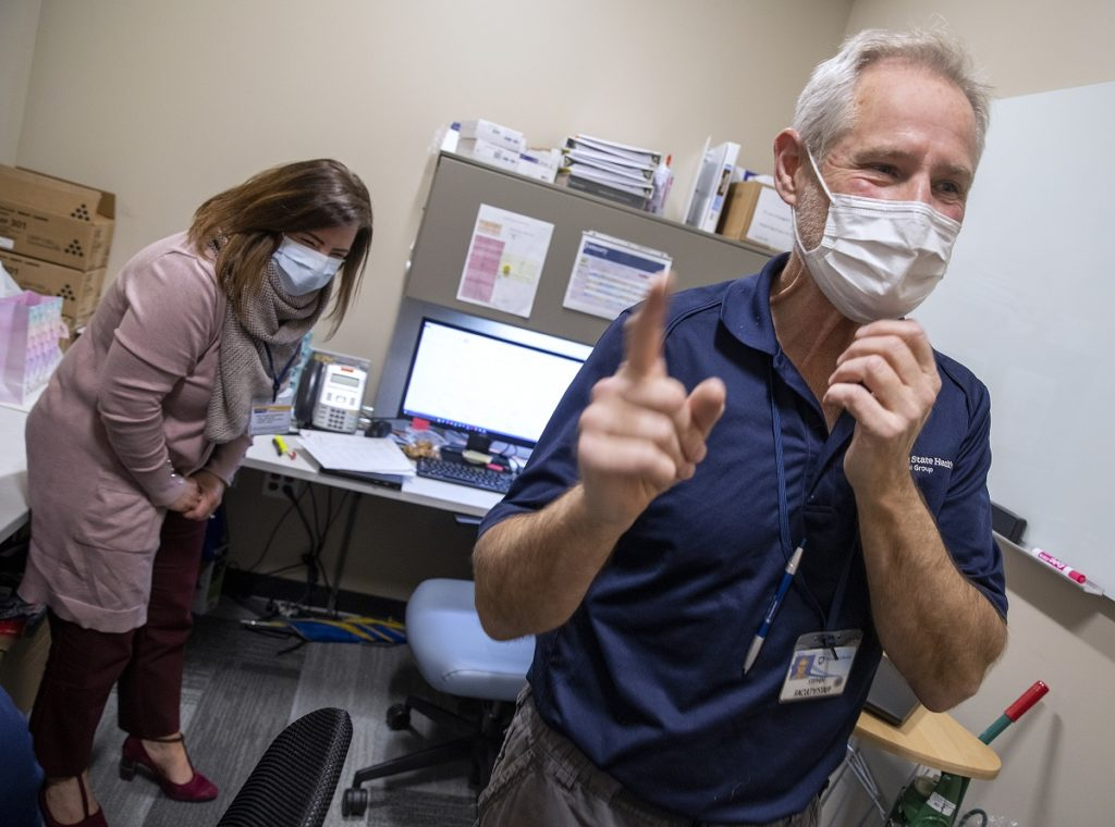 Caldwell, right, points a finger and laughs as Diane Bournelis, a senior administrative assistant, leans over, laughing, in an office at Lime Spring Outpatient Center. He is wearing a polo shirt with the Penn State Health logo on it, a name badge and a face mask. Bournelis is wearing a sweater, pants and face mask. A desk with a computer monitor is behind Caldwell.
