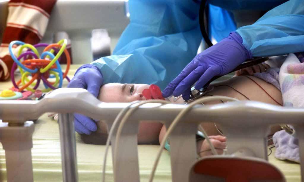 Los guantes de goma y la bata de un trabajador de salud se pueden ver sosteniendo el extremo de un estetoscopio en el pecho de un bebé. El bebé tiene un chupete y mira hacia adelante con los ojos medio tapados.