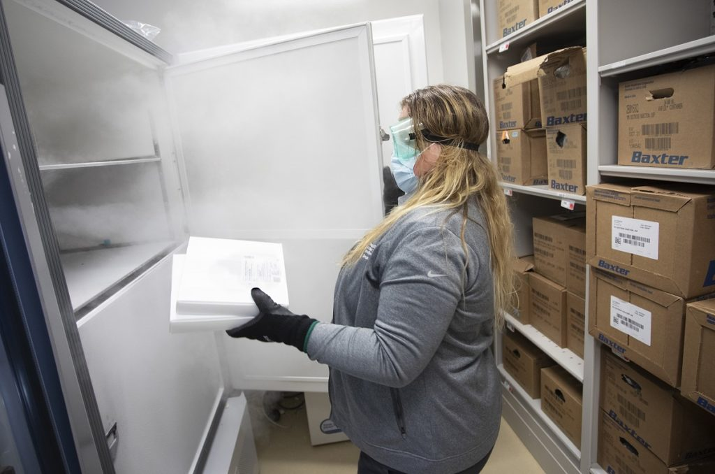Raven Dailey, a pharmacy buyer at Hershey Medical Center, stores a package of COVID-19 vaccinations in the freezer at the pharmacy.