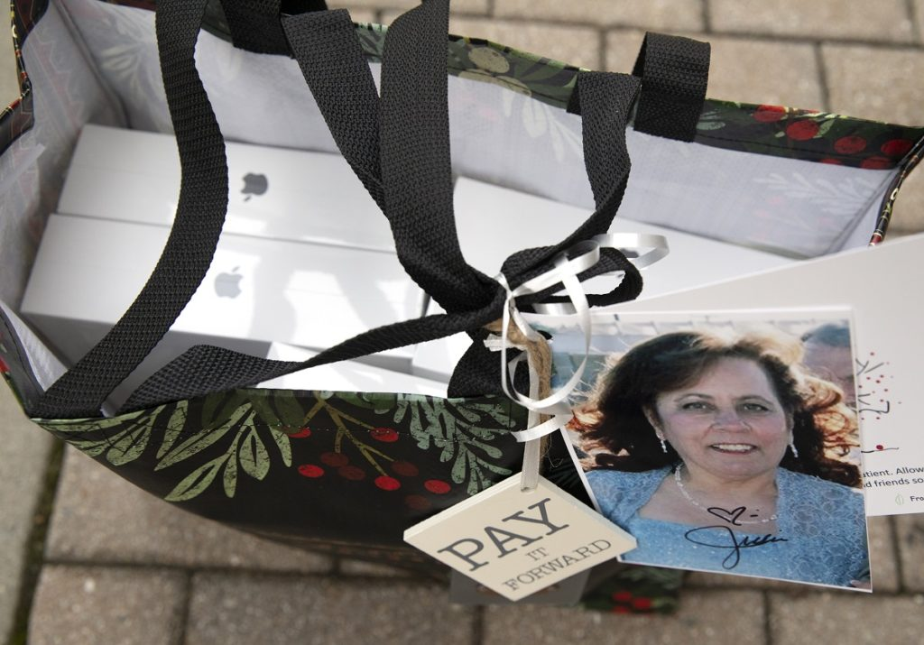 """The contents of a bag include several boxes with the iPad logo, the picture of a woman and a tag that says """"Pay it Forward."""""""
