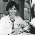 Mary Simmonds sits at a desk wearing a lab coat and stethoscope