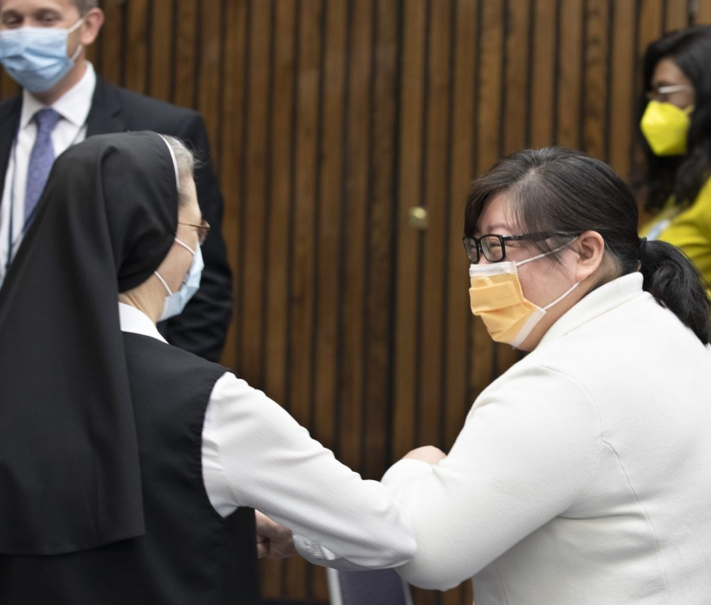 A woman dressed in a white blouse, black veil and tunic and wearing glasses and a blue face mask, bumps elbows with a woman dressed in a white coat and wearing glasses, an orange face mask and ponytail.