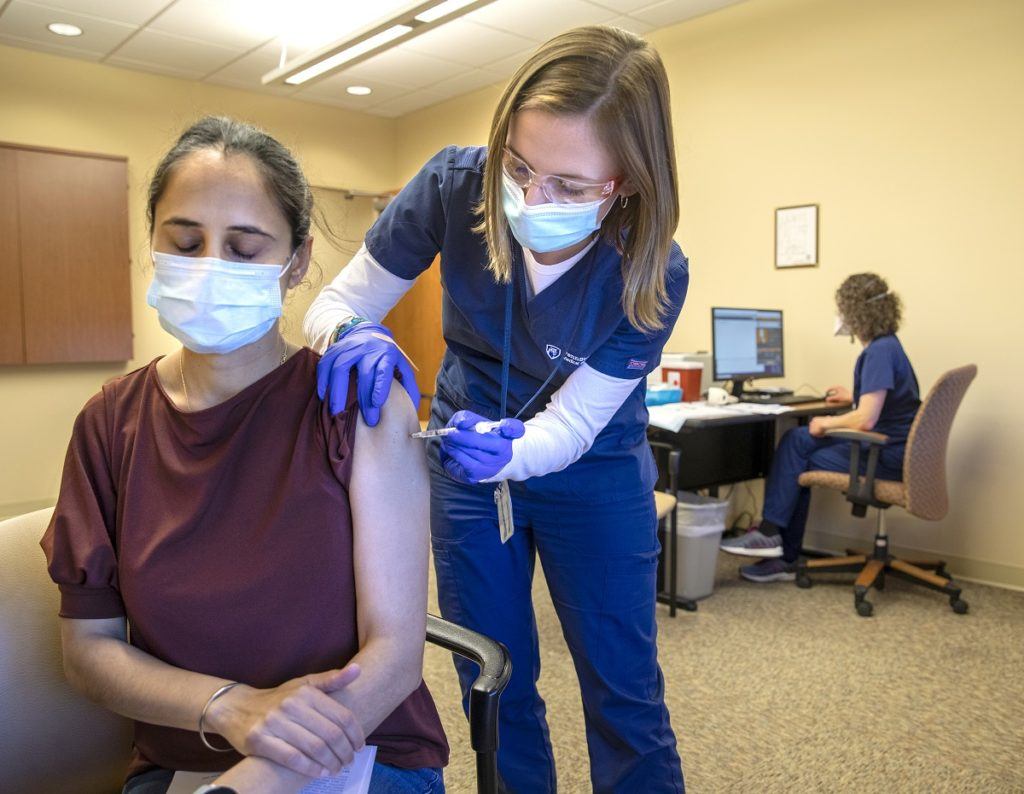 Julianne Callis, right, of Holy Spirit Medical Center's Employee Health Services Department, gives a COVID-19 vaccination to physical therapist Satvir Gill. Callis is wearing scrubs with the Penn State Health logo on them, goggles and rubber gloves. Gill is wearing a short-sleeved shirt and has her eyes closed. Both are wearing face masks.