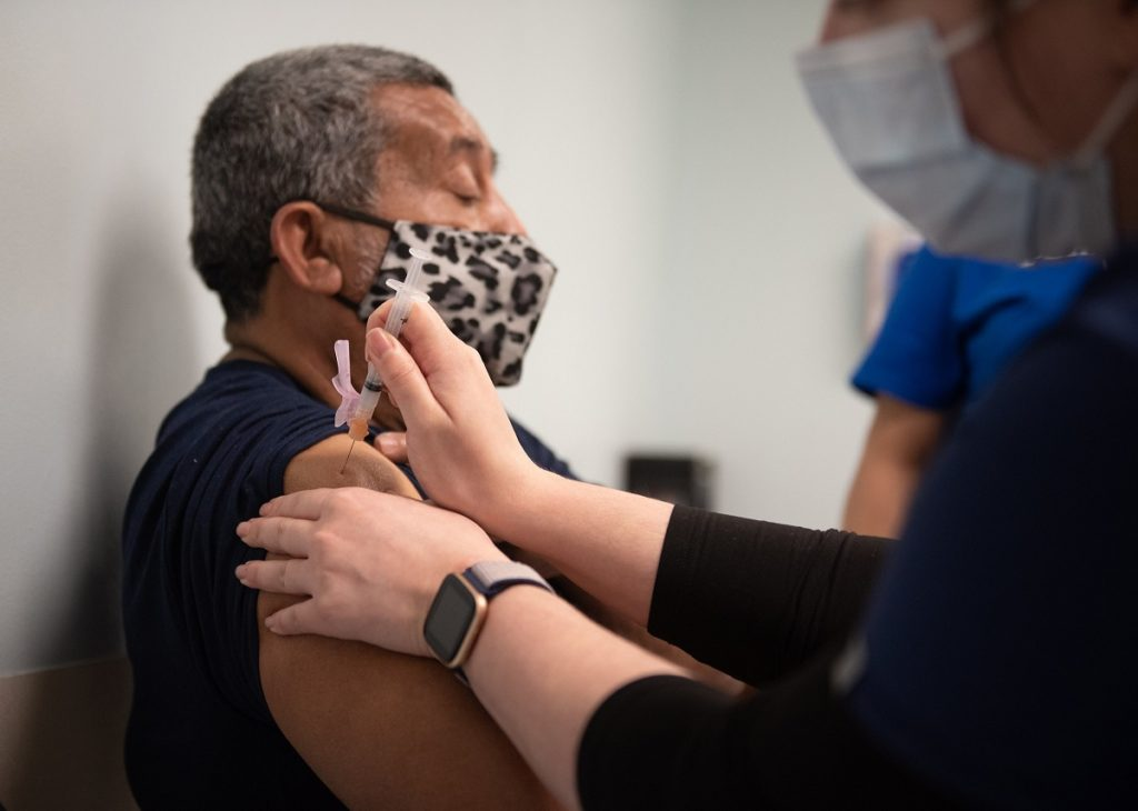 Samuel Garcia, who is seated and wears a mask, looks straight ahead as he receives a COVID-19 vaccine into his upper arm from a health care worker.