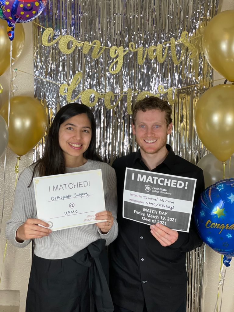 Nate Tolman, a fourth-year medical student at Penn State College of Medicine, and Brenda Iglesias hold up signs saying they matched to residency programs at University of Pittsburgh Medical Center.